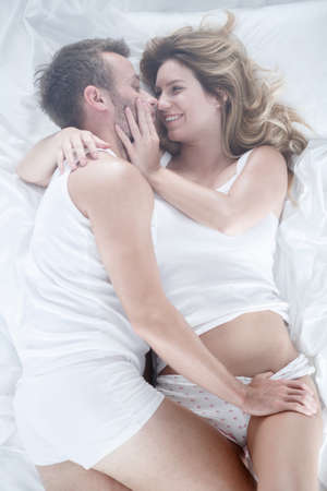 sex tenderness: Image of boyfriend and girlfriend having fun lying in bed Stock Photo