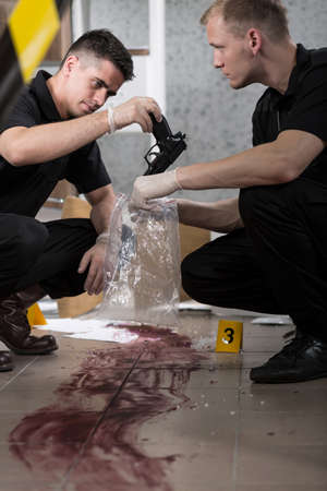 gun man: Policeman preventing handgun at the murder scene
