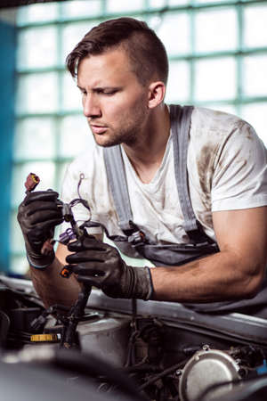 diagnosing: Portrait of focused automobile repair shop worker diagnosing problem
