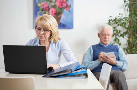 Elderly busy married couple working at home