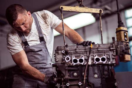 修理店の起重機に掛かっている車のエンジンの写真