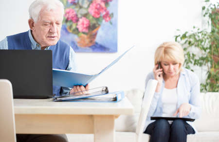 important: Elder businesspeople checking important docuemnts of their company Stock Photo