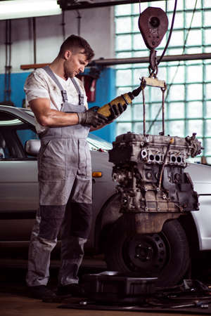 Picture of auto mechanic inspecting broken motor car