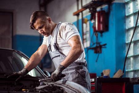주유소에서 일하는 전문 제복 자동차 정비공의 이미지