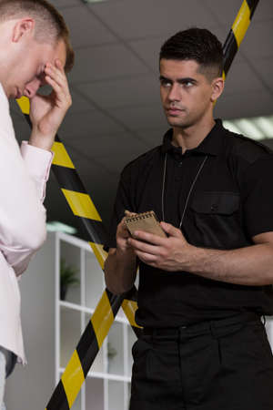 constabulary: Despair man talking with policeman at the crime scene Stock Photo