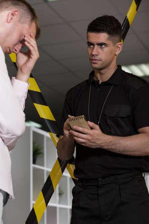 criminal investigation: Despair man talking with policeman at the crime scene Stock Photo