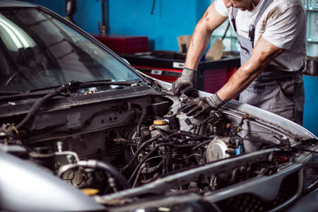 mecanico: Imagen del mecánico de automóviles uniformado mantiene el motor de coche Foto de archivo