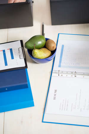 folder with documents: Close-up of folder with documents and healthy snack on desk