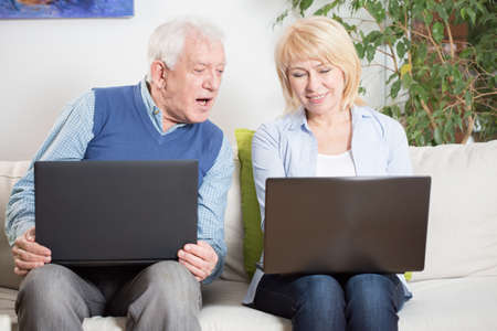 learning computer: Elderly woman teaching her surprised husband using laptop