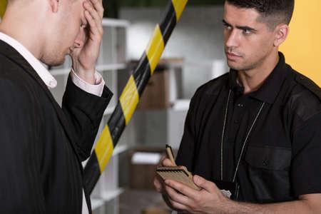 interrogating: Despair man and policeman at the murder scene