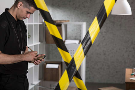 caution tape: Policeman and barricade tape at the crime scene Stock Photo