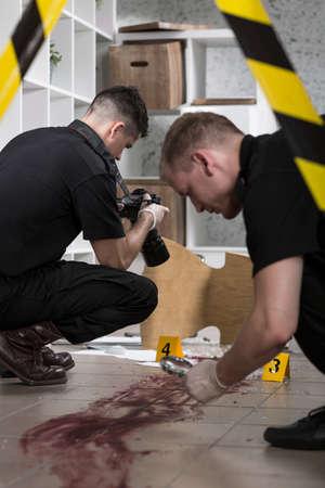 murder scene: Close-up of policemen working at the murder scene Stock Photo