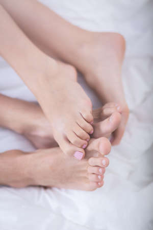 sex tenderness: Close up of feet of romantic couple lying in bed