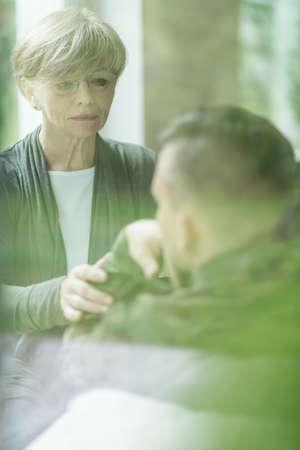 psychiatrist: Image of female psychiatrist comforting military patient Stock Photo
