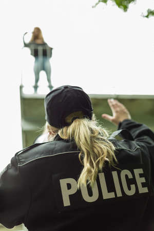 policewoman: Picture of policewoman with megaphone helping suicide girl Stock Photo