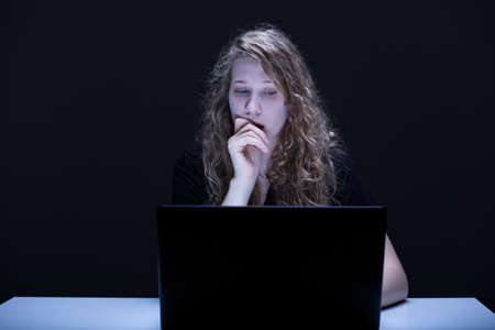 teary: Photo of frightened and teary female using computer Stock Photo