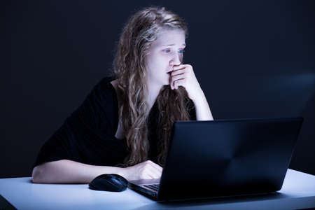 scared girl: Picture of despair scared girl suffering from electronic aggression Stock Photo