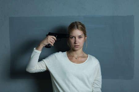 mujer con pistola: Retrato de niña desesperada celebración de arma de fuego en la cabeza
