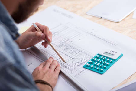 Architect with blueprint and calculator estimating project cost
