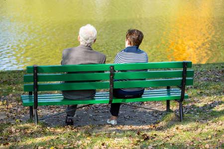personas sentadas: Parte posterior de la pareja de ancianos sentados en el lago