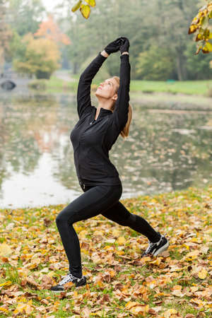 stretch out: Training yoga in park in autumn day Stock Photo