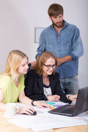 graphics design: Chief and employees sitting at the desk and working together Stock Photo