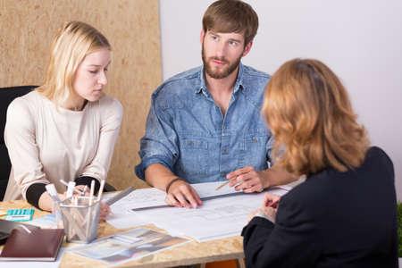 gente trabajando: jóvenes arquitectos y clientes en discusiones sobre el proyecto