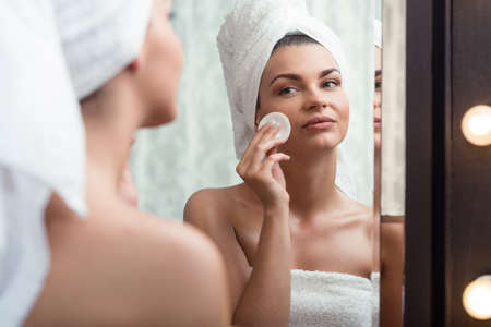 若い美しさ女性トイレで化粧を削除します。