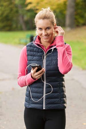 escuchando musica: Mujer de la belleza con ropa deportiva y escuchar música