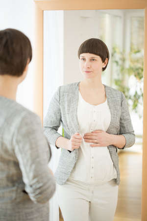 woman looking: Elegant young gravid woman looking at herself in the mirror