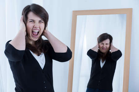 dissimulation: Screaming angry woman and her reflection in the mirror Stock Photo