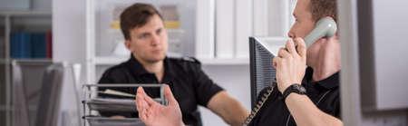 clavados: Panorama de policías jóvenes que trabajan en la oficina Foto de archivo