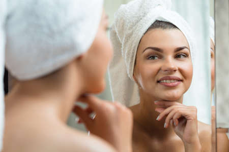 girl with towel: Beautiful and smiling woman looking at the mirror