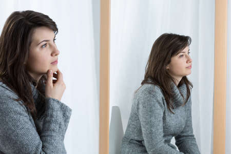 reflection in mirror: Picture of bored woman masking her emotions