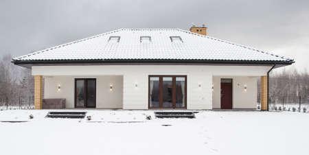 Fachada: Imagen de la casa unifamiliar y los árboles cubiertos de nieve