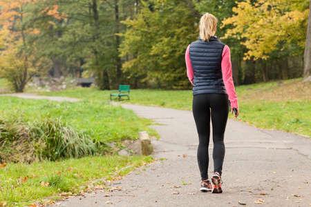 Fit woman walking in park during autumn time Foto de archivo