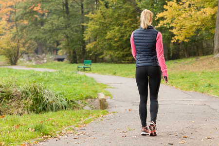 atleta: Montar una mujer caminando en el parque durante el oto�o de tiempo