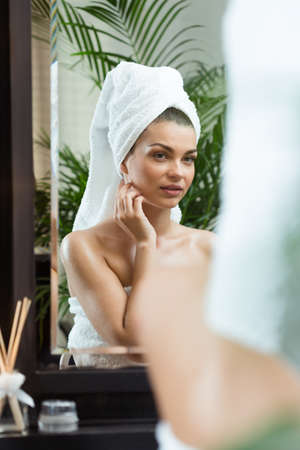 woman in the mirror: Woman admiring her reflection in the mirror Stock Photo