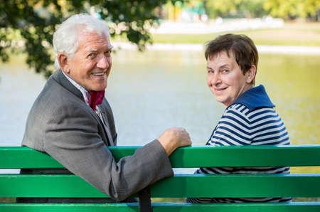 abuela: Marido y mujer de edad avanzada sentado en el lago