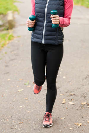 run out: Close-up of sporty woman running with dumbbells Stock Photo