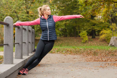 stretch out: Beauty active woman training in park at autumn day Stock Photo