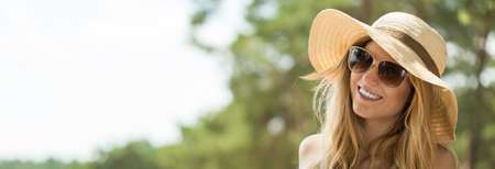 panorama: Panoramic picture of smiling girl in panama hat and sunglasses Stock Photo