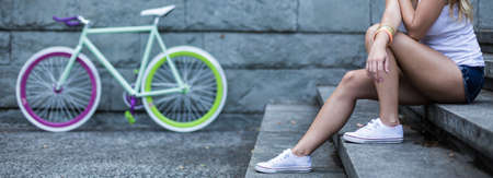 Girl sitting on the steps with bicycle in background