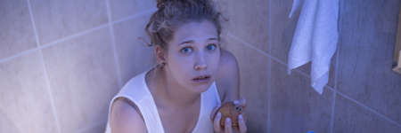 bulimia: Young girl with bulimia is hiding in bathroom with food