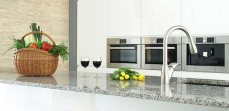 counter top: Modern kitchen interior with vegetables, glasses of wine and flowers
