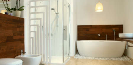 Modern en suite bathroom with free standing bath and travertine tiles.