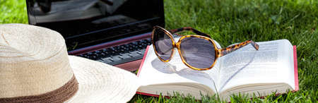 cover page: Hat, book, sunglasses and notebook on a grass