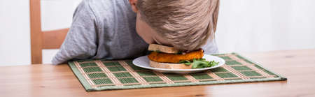 eater: Boy is fooling around at the table