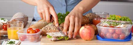 bocadillo: Una persona cortar un sándwich mientras que hace un almuerzo saludable