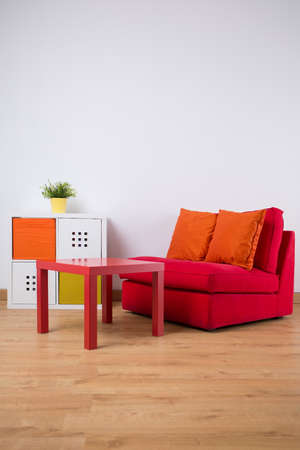 sofa: Photo of small red table and double sofa with cushions